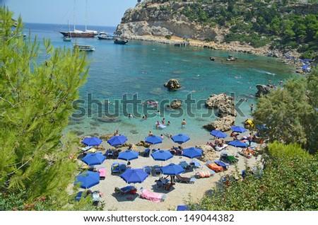 Antony Queen or Quinn  beach Rhodes Greece - trees umbrellas - stock photo