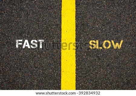 Antonym concept of FAST versus SLOW written over tarmac, road marking yellow paint separating line between words - stock photo
