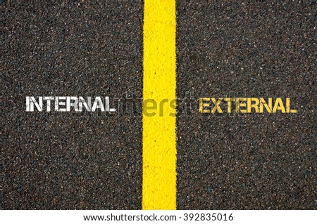 Antonym concept of INTERNAL versus EXTERNAL written over tarmac, road marking yellow paint separating line between words - stock photo
