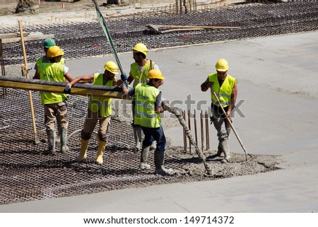 ANTWERP, BELGIUM - JULY 9: Workers pouring concrete for the bases of the new Antwerp Port Authority HQ on July 9, 2013 in Antwerp, Belgium. The new building will be build over a monumental building. - stock photo