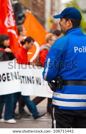 ANTWERP, BELGIUM - MAY 1: A unidentified friendly Flemish Policeman smiles and watches over marchers at the annual May Day Parade on May 1, 2010 in Antwerp, Belgium - stock photo