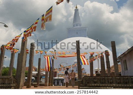ANURADHAPURA, SRI LANKA - MAY 19, 2011: Unidentified people enjoy the view to the Ruwanwelisaya stupa. Ruwanwelisaya is a sacred place for Buddhists and one of the largest stupas in the world.