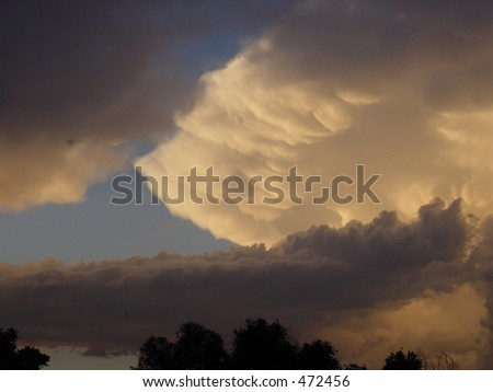 Anvil peeks through lower storm clouds - stock photo