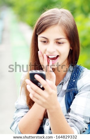 anxcios young girl looking at phone seeing bad news or photos there with disgusting emotion on her face - stock photo