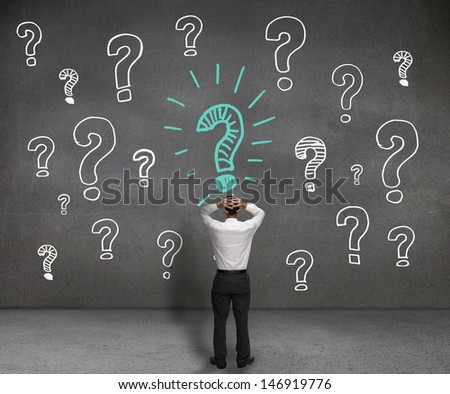 Anxious businessman looking at a drawing of question marks - stock photo