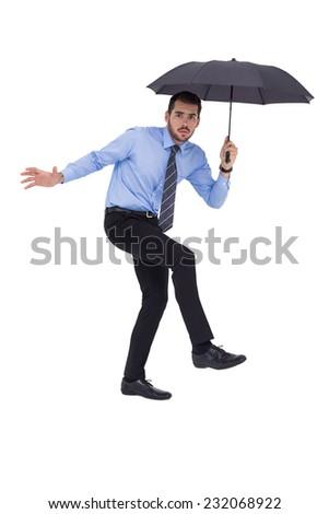 Anxious businessman under umbrella balancing on white background - stock photo