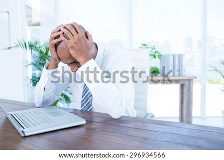 Anxious businessman with head in hands at office - stock photo