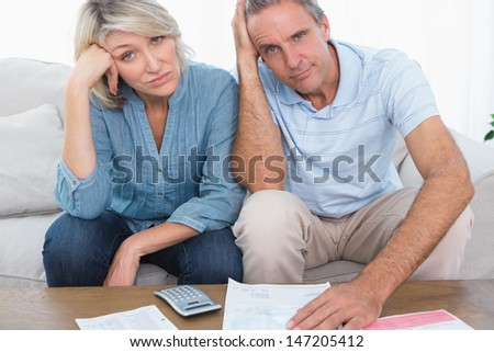 Anxious couple going over bills looking at camera at home in living room - stock photo