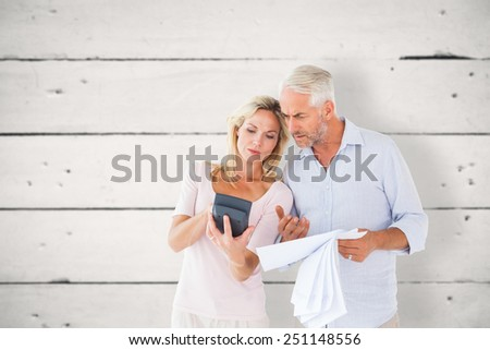 Anxious couple working out their bills against white wood - stock photo