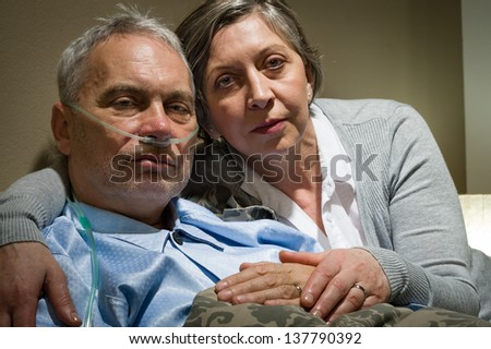 Anxious senior wife holding her sick husband at clinic - stock photo