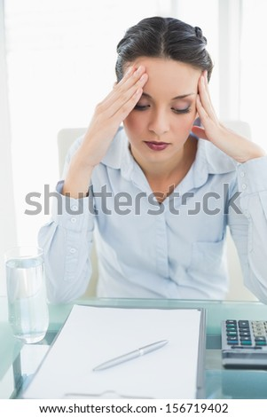 Anxious stylish brunette businesswoman holding her head in bright office - stock photo