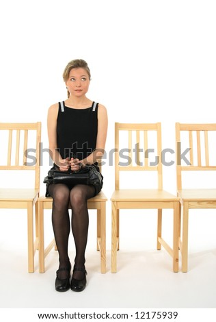 Anxious young lady sitting on a chair and waiting. - stock photo