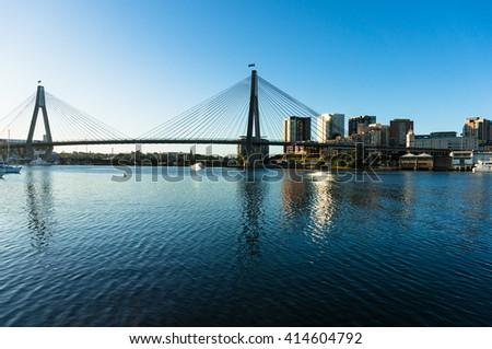 ANZAC Bridge with australian flags and Sydney CBD cityscape at dusk, Sydney, NSW, Australia - stock photo