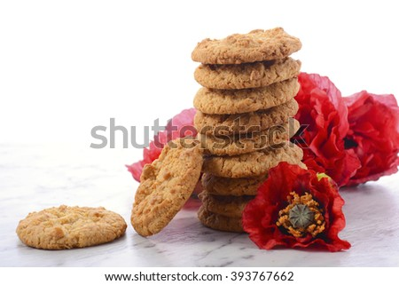 ANZAC Day, April 25, traditional Anzac biscuits on white marble table with red poppies.   - stock photo