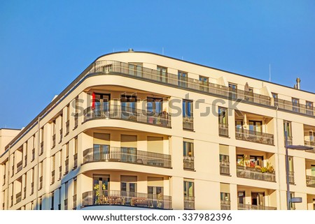 Apartment building facade with balconies, urban - blue sky - stock photo