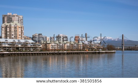 Apartment Buildings on the waterfront of New Westminster Downtown. Fraser River, Bridge and mountain view.