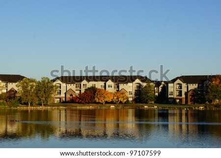Apartment Complex Building on the Lake during fall autumn season - stock photo