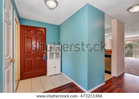 Apartment hallway interior with blue walls, tile and wood flooring. Brown front door and white cabinet. Northwest, USA