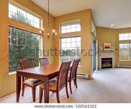 Apartment interior with yellow walls, high ceiling and large windows. Open floor plan. Close up of Dining table set. Northwest, USA