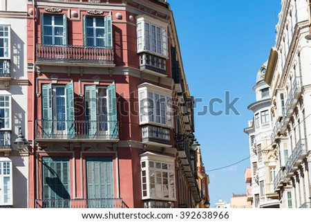 Apartments with small balconies typical architecture.  Low angle view down street of apartments with small balconies in the city of Malaga in Spain under clear blue sky - stock photo