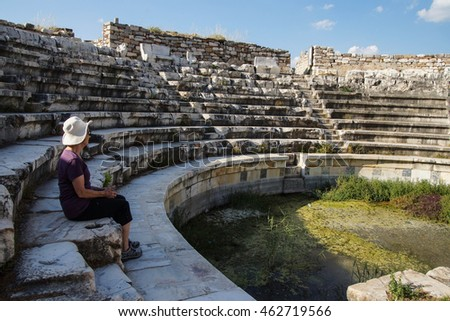 APHRODISIAS, TURKEY, - MAY 26, 2014 - Tourist sits in the ruins of the  odeon Boulouterion Aphrodisias,  Turkey