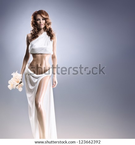 Aphrodite styled young woman over grey background with some blank space - stock photo