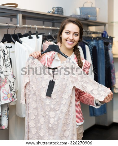 Apparel shop: attractive young woman renewing her wardrobe - stock photo