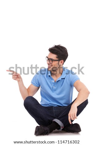 appealing casual young man sitting on the floor, pointing and looking to his side while smiling - stock photo