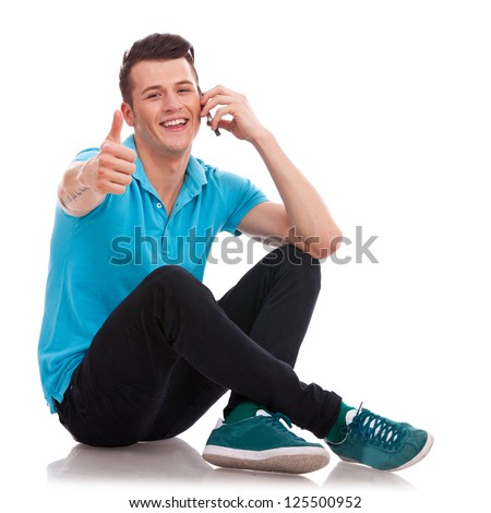 Appealing casual young man sitting with his legs crossed and showing thumbs up sign, while speaking on the phone and smiling to the camera. Isolated on white background - stock photo