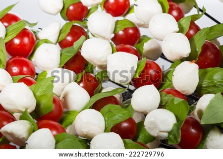 Appetizer. baby mozzarella with cherry tomatoes and basil leaves. Creative cuisine. close-up - stock photo