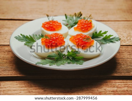 Appetizer boiled eggs half with red salmon caviar and parsley on plate on a wooden background - stock photo