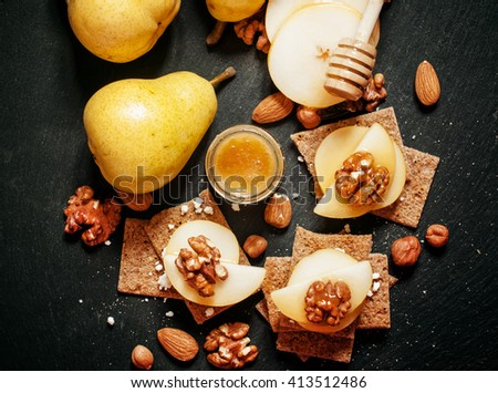 Appetizer canape with pear, honey, hazelnuts, almonds and cottage cheese. dark background, top view - stock photo