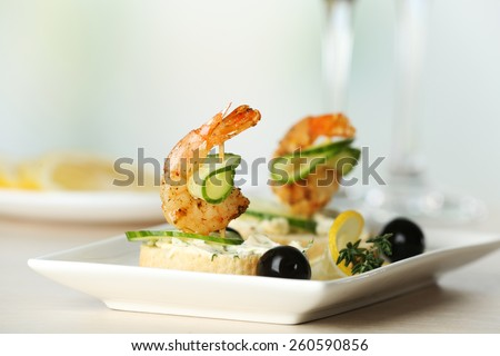 Appetizer canape with shrimp and olives on table on light background - stock photo