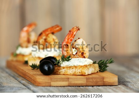 Appetizer canape with shrimp and olives on wooden background - stock photo