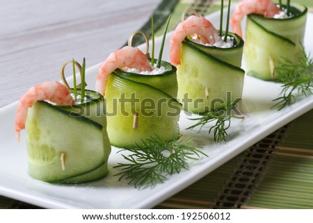 appetizer of cucumber rolls with shrimp and cream cheese closeup on a white plate. horizontal   - stock photo