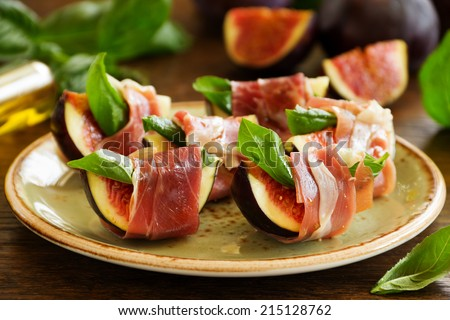 Appetizer of figs and prosciutto. - stock photo