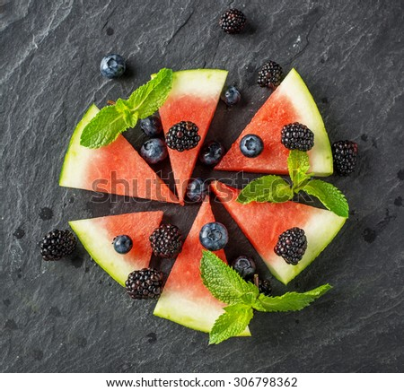 Appetizer of juicy watermelon, ripe blackberry and fresh blueberries on a black stone chilled board. The concept of healthy natural foods. Top view. selective Focus - stock photo