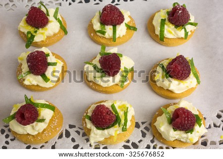 appetizer of mascarpone cream with lemon zest and cut mint leafs on a tapas cracker decorated with raspberry - shallow DOF - stock photo