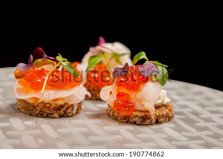 Appetizer of Salmon eggs, fish, and green herbs canapes