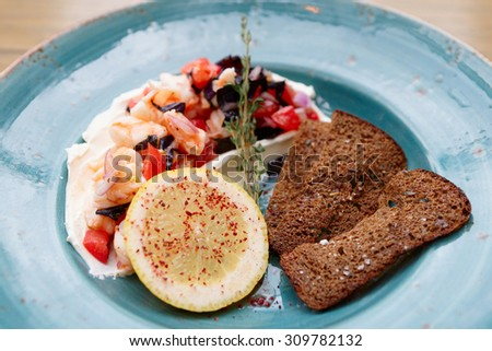 Appetizer of shrimps, tomatoes and sour cream with rye bread toasts - stock photo