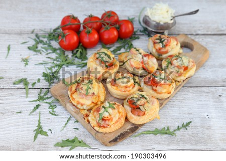 Appetizer of vegetables and meat on the puff pastry with Parmesan cheese on a wooden background. Food style. Tart. - stock photo