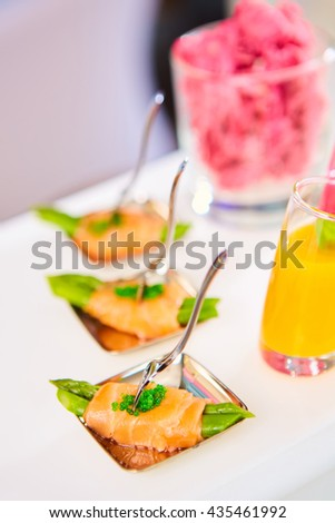 Appetizer plate of sauteed asparagus wrapped in thin slices smoked salmon - stock photo