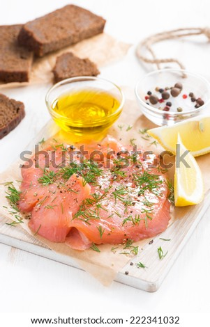 appetizer - salted salmon and bread on a wooden board, vertical, close-up - stock photo