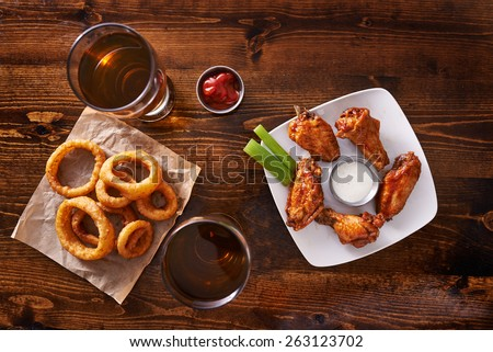 appetizer sampler with onion rings and chicken wings shot top down - stock photo