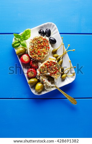 appetizer tray of green olives, black olives, capers, buffalo mozzarella, artichokes and red Chili  peppers filled with tuna on blue - stock photo