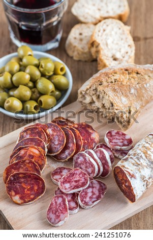 Appetizer with slices of sausage (chorizo), olives, bread and wine - stock photo