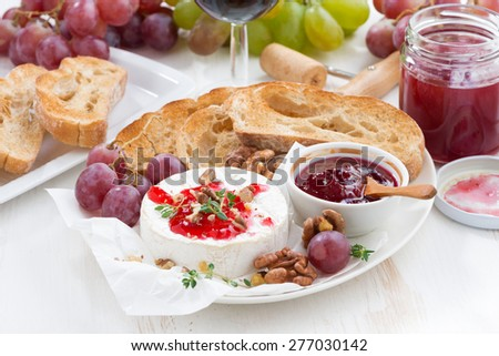 appetizers for wine - camembert with berry jam, toast and fruit, close-up, horizontal - stock photo