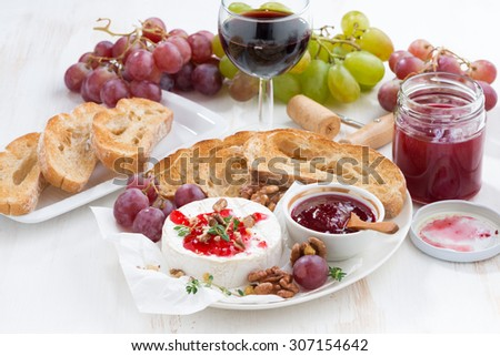 appetizers for wine - camembert with berry jam, toast and fruit, horizontal - stock photo
