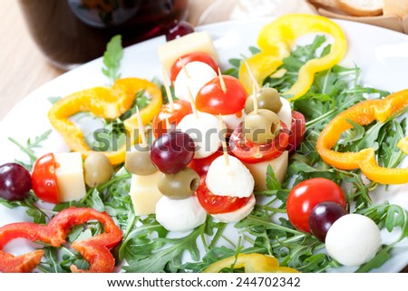 Appetizers made of skewers with cheese, olive, grape, and tomatoes, served on plate with fresh rocket and slices of sweet pepper, vine and bread in background