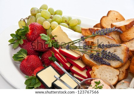 Appetizers selection with strawberries, bread, grapes and cheeses on a  platter at an event - stock photo
